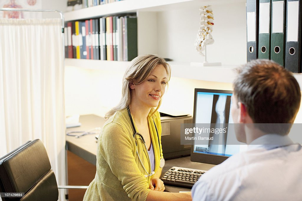 Doctor talking over x-ray with patient in doctors office : Stock Photo