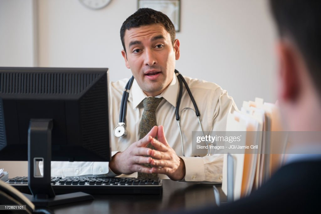 Doctor talking to clients in office : Stock Photo