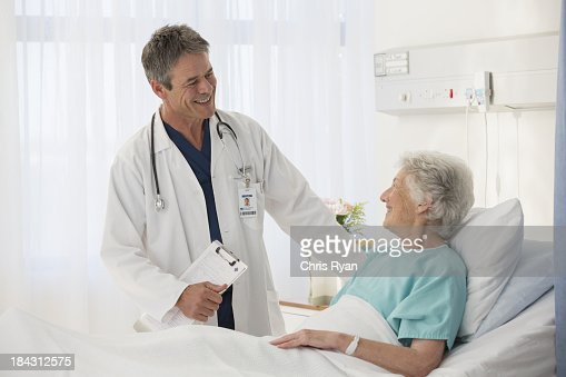 Doctor talking to elderly patient in hospital