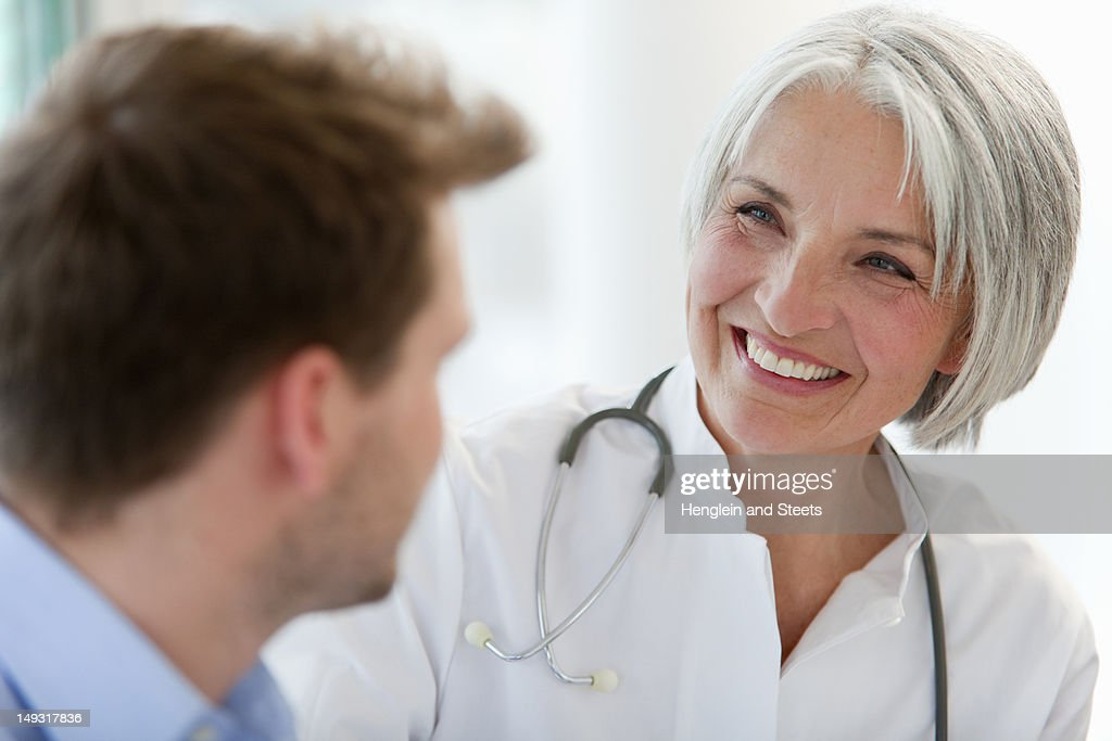 Doctor talking to man in office : Stock Photo