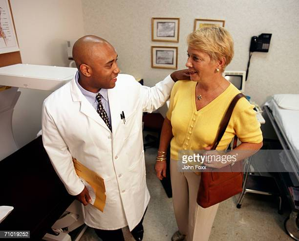 Doctor talking to patient in clinic, smiling, high angle view