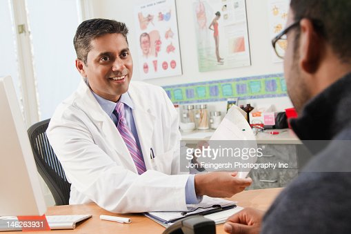 Doctor talking to patient in doctor's office : Stock Photo