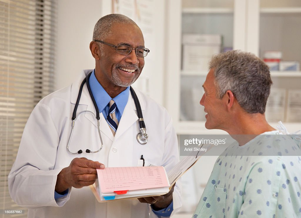 Doctor talking to patient in examination room : Stock Photo