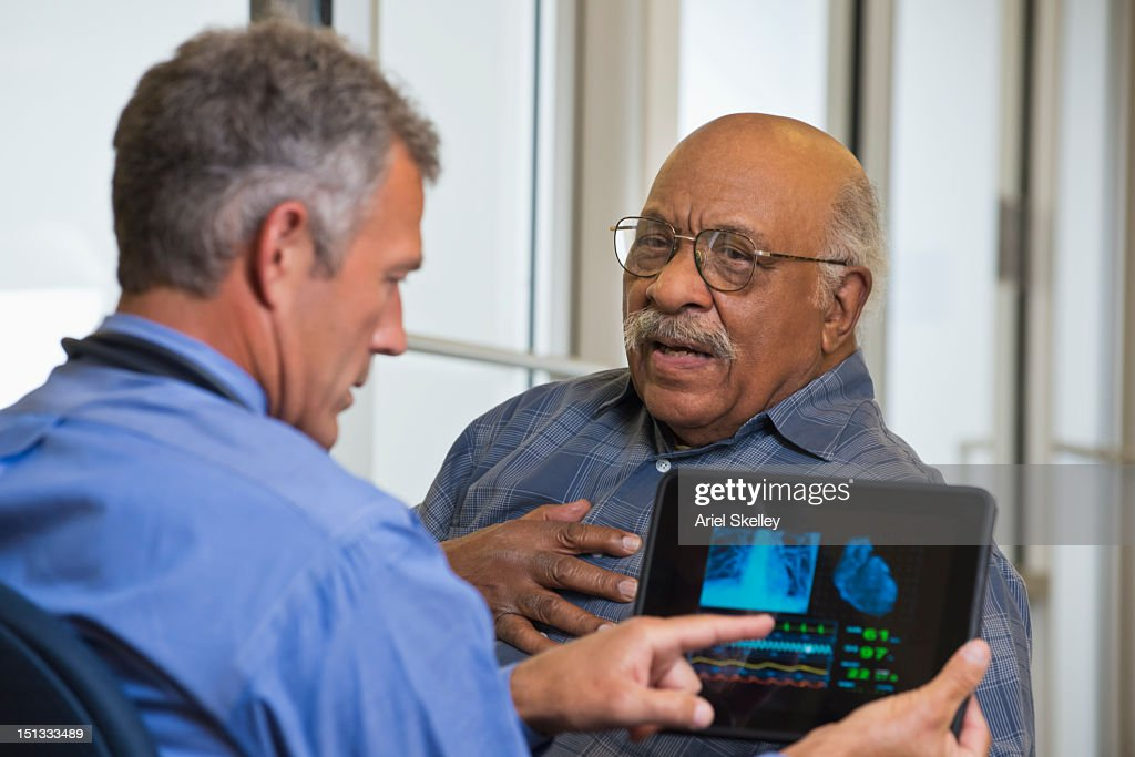 Doctor talking to patient in hospital using digital tablet : Stock Photo