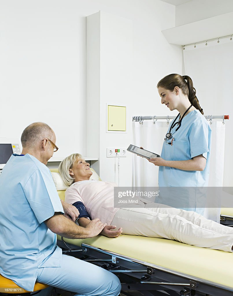 doctor talking to patient, using digital tablet : Stock Photo