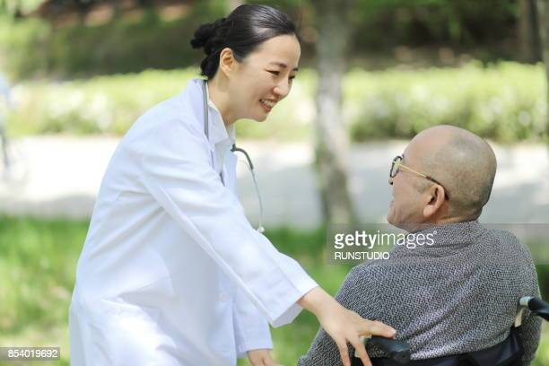 Doctor talking to senior man in wheelchair