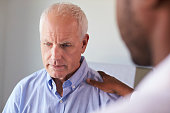 Doctor Talking To Unhappy Male Patient In Exam Room