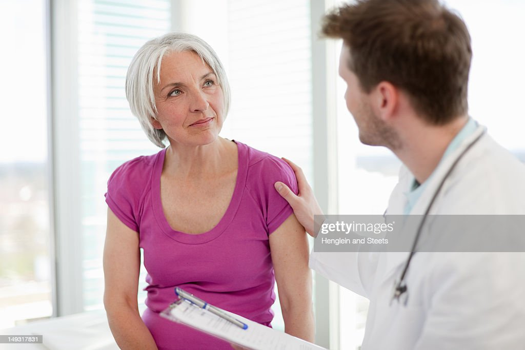 Doctor talking to woman in office : Stock Photo