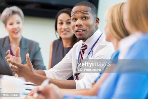 Doctor talking with hospital board members during meeting