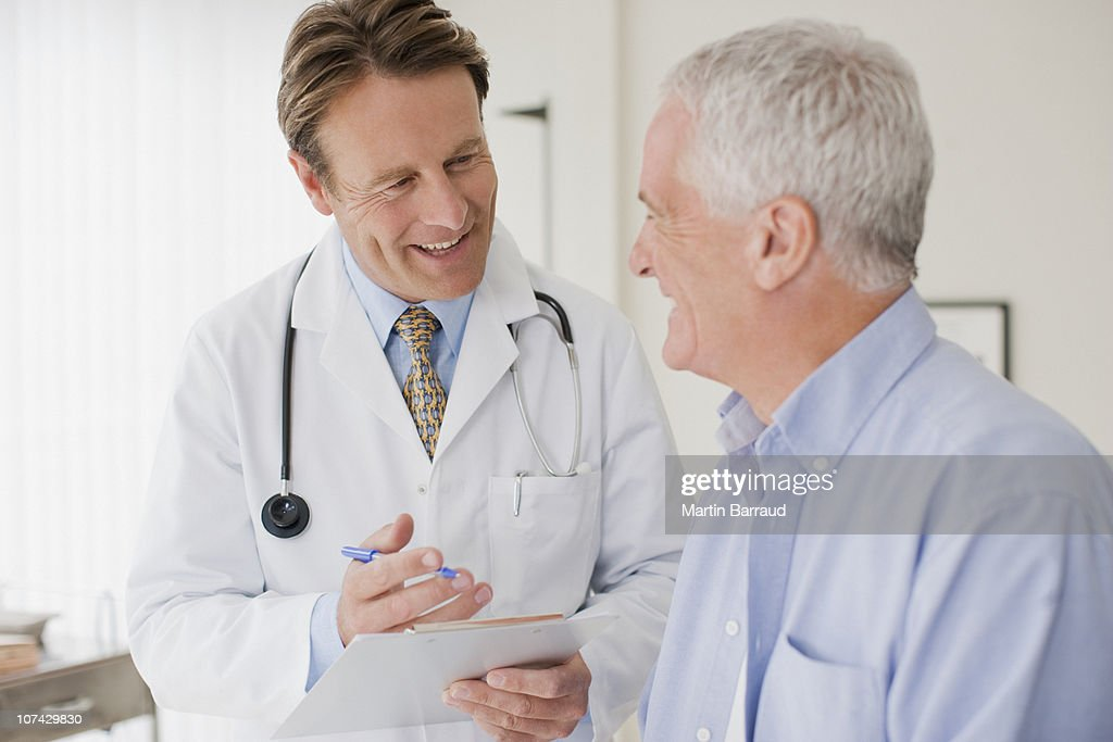 Doctor talking with patient in doctors office : Stock Photo