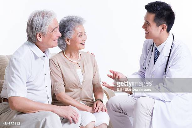 Doctor talking with senior couple
