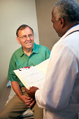 A doctor talks with a patient while holding his medical file during an exam