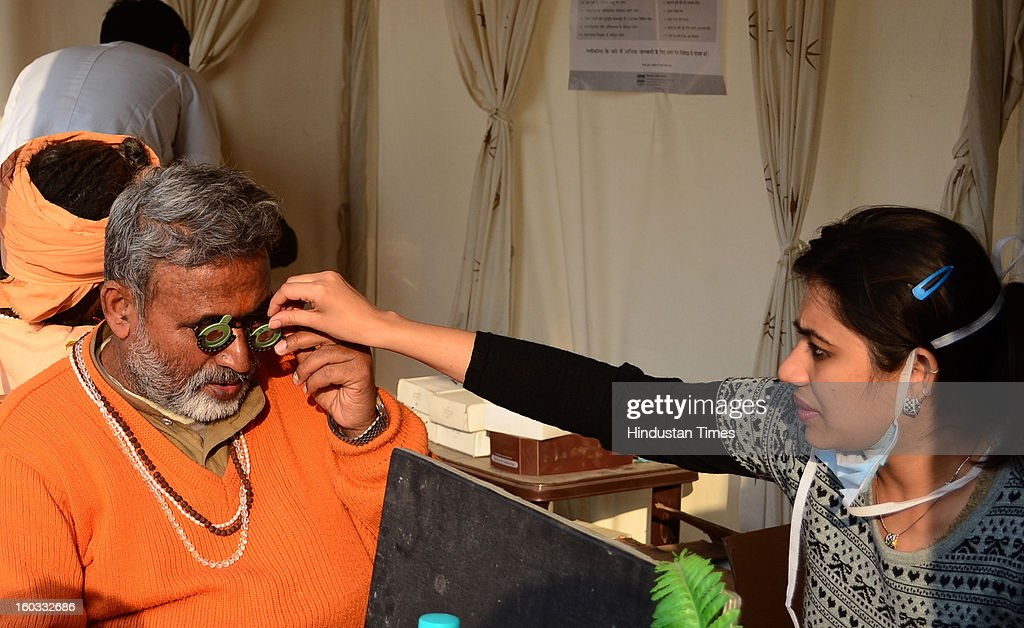 A doctor test eyes of a Sadhu at one of the free health camp in Agni Akhara, in a Kumbh Mela area, on January 29, 2013 in Allahabad, India. Millions of Hindu devotees have begun their month-long kalpvas at the tent city set up over 58 square kilometers and divided into 14 sectors inter-connected using 17 pontoon bridges.