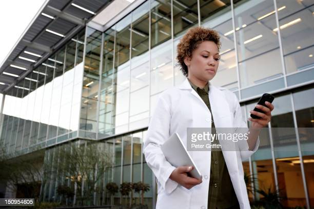 Doctor text messaging on cell phone