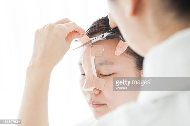Doctor to taping a patient's nose