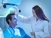 Doctor treating patient using magnetoencephalography (MEG) scanner