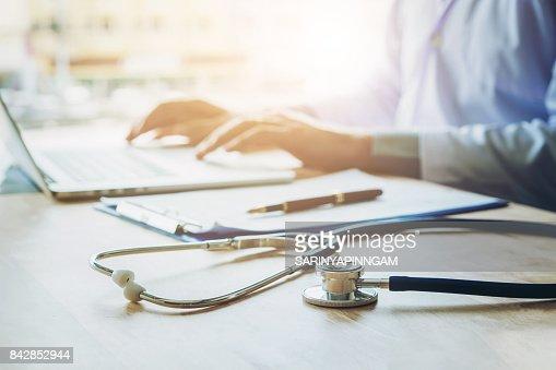 Taper des informations sur ordinateur portable en bref Bureau hôpital le stéthoscope de docteur : Photo
