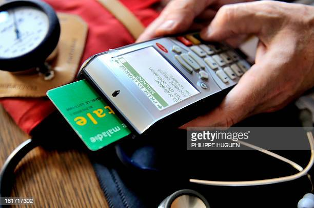 A doctor uses a French health insurance electronic card in a connected reader on September 23 2013 in Godewaersvelde northern France during medical...