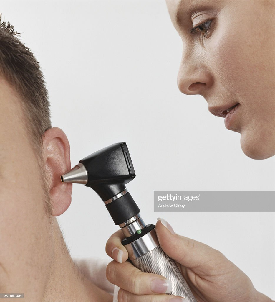 Doctor Using an Otoscope to Examine a Patients Ear : Stock Photo
