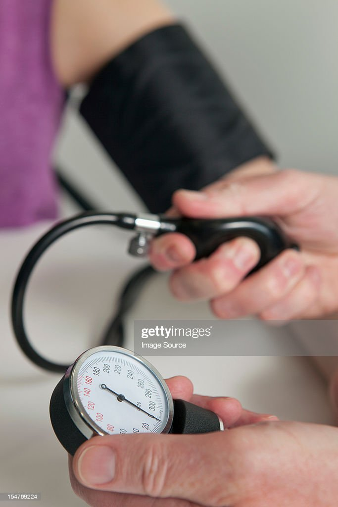 Doctor using blood pressure gauge on patient during medical examination