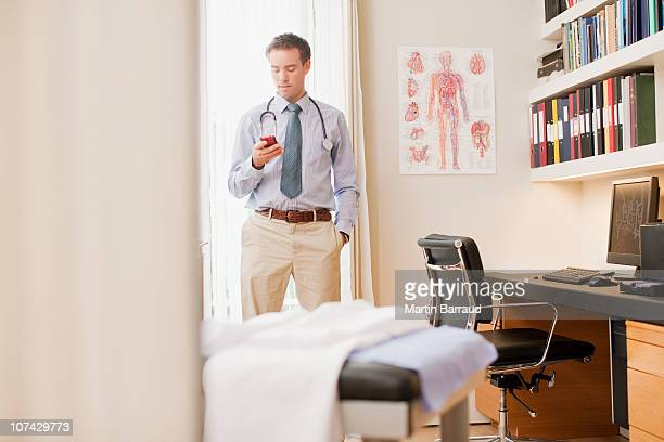 Arzt mit Handy in Arzt-Büro