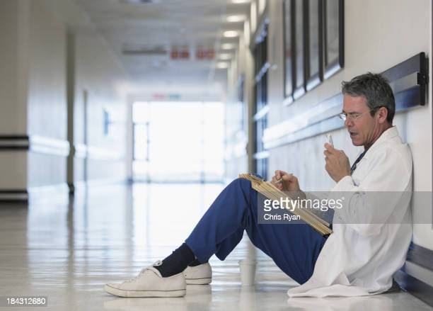 Doctor using dictaphone in hospital corridor