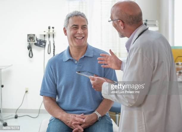 Doctor using digital tablet and talking to patient in office