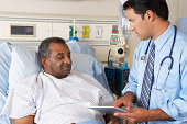 Doctor Using Digital Tablet In Consultation With Senior Patient