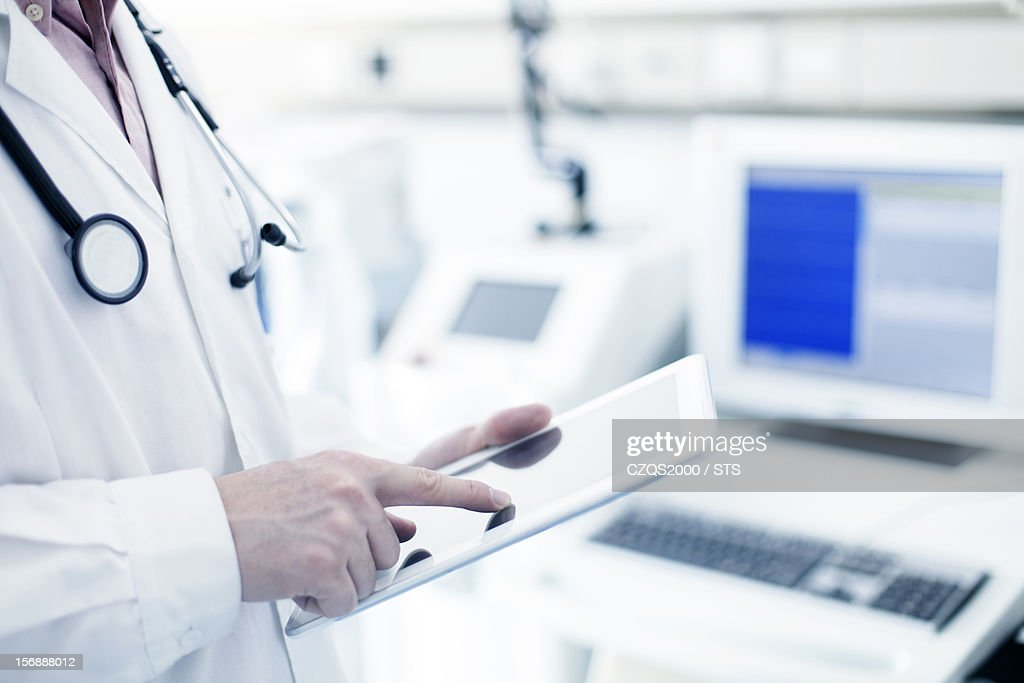 Doctor using digital tablet in hospital : Stock Photo