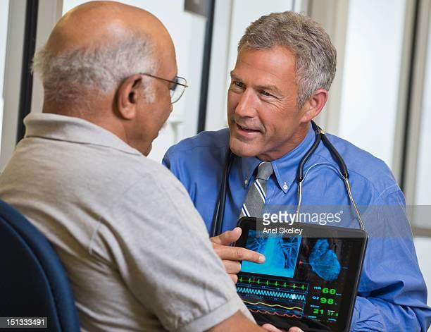 Arzt mit digitalen tablet sprechen, geduldig