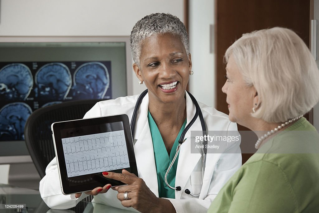 Doctor using digital tablet while talking to patient : Stock Photo