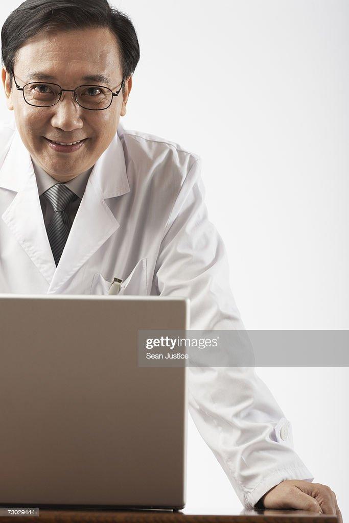 Doctor using laptop, portrait : Stock Photo