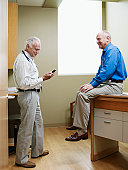 Doctor using mobile while senior male patient sitting in exam room, smiling
