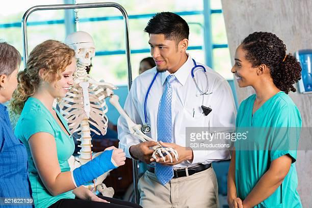 Médecin à l'aide du modèle de skeleton expliquer les blessures au patient un os