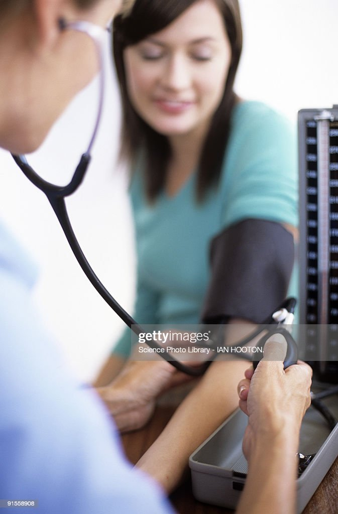 Doctor using sphygmomanometer and stethoscope to measure patient's blood pressure