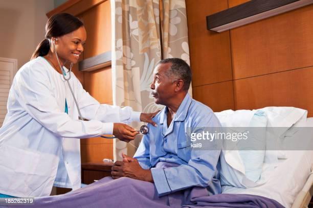 Doctor using stethoscope on senior patient