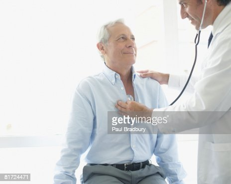 Doctor using stethoscope on smiling patient : Stock Photo