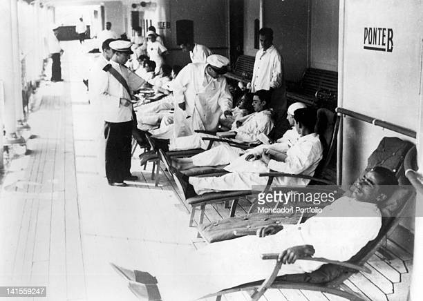 Doctor visiting injured soldiers on the deck of a hospital ship returning from Libya Italy August 1940