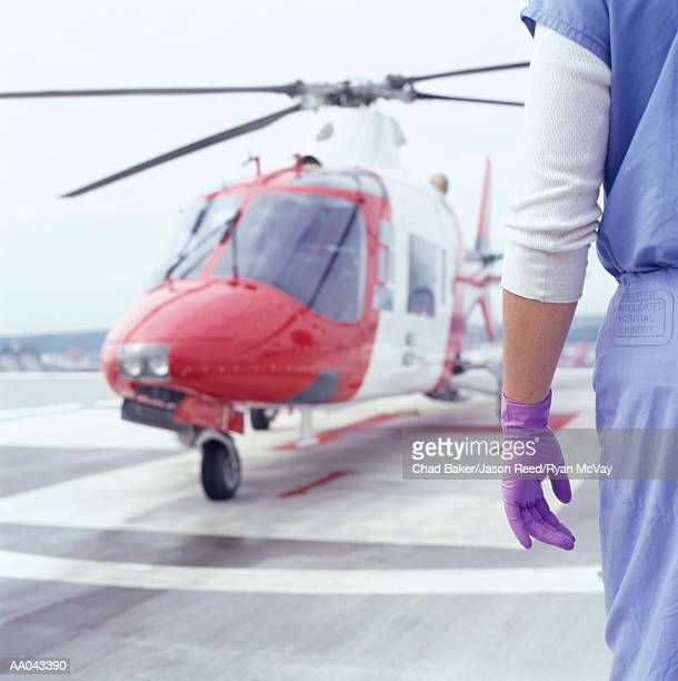 Doctor waiting on tarmac for medivac, rear view