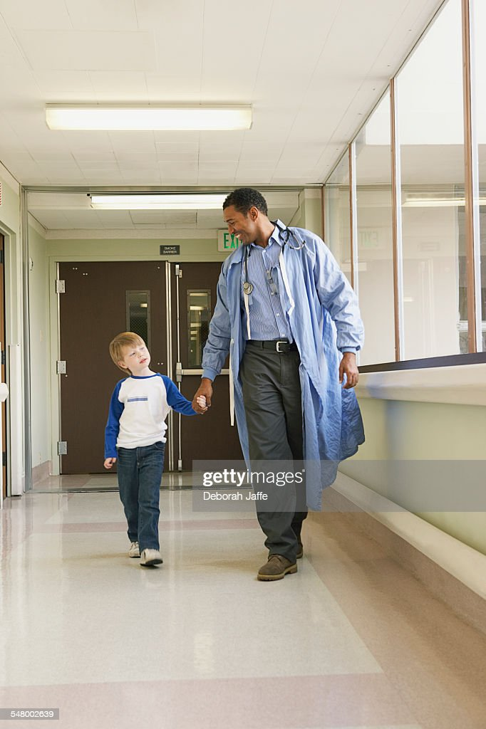 Doctor walking with patient : Stock Photo