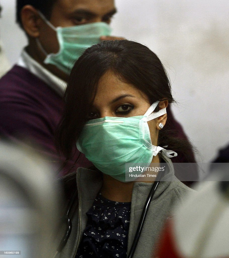 Doctor wearing a mask as a precaution measure against swine flu virus, attends a patient at a RML hospital on February 8, 2013 in New Delhi, India. According to local reports, 64 cases have been reported so far out which three persons infected with swine flu have died.