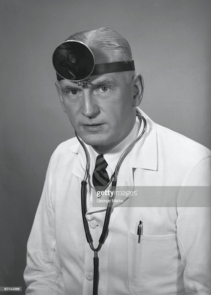 Doctor wearing headlamp posing in studio, (B&W), portrait : Stock Photo