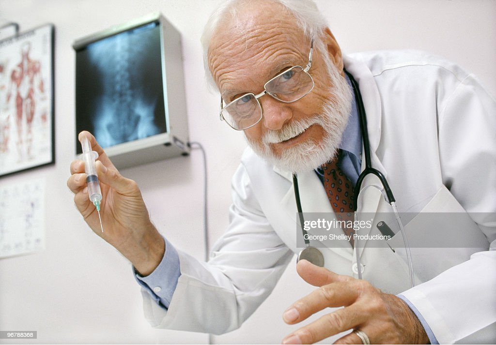 Doctor with a hypodermic needle in hand : Stock Photo
