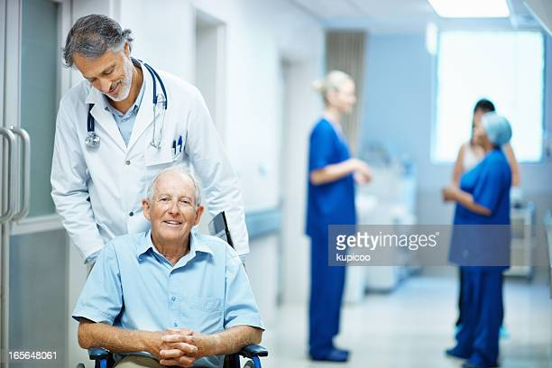 Doctor with an old man sitting in wheelchair