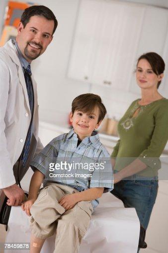 Doctor with boy showing adhesive bandage on leg : Stock Photo