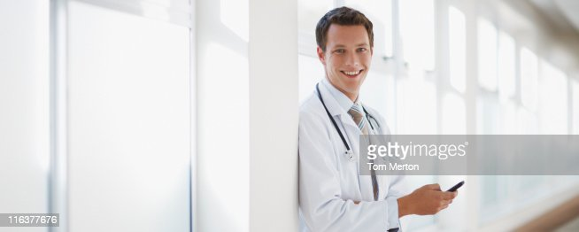 Doctor with cell phone in hospital corridor : Stock Photo