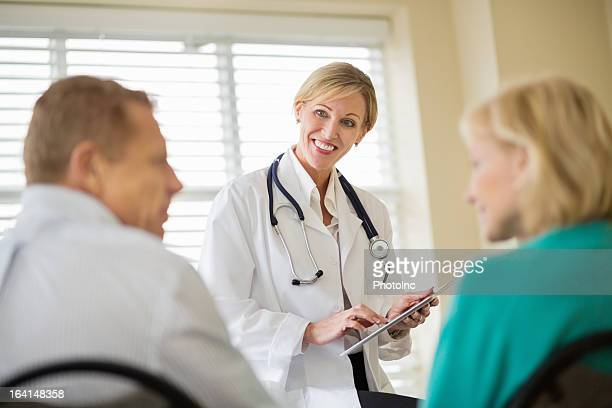 Doctor With Digital Tablet Looking At Patients