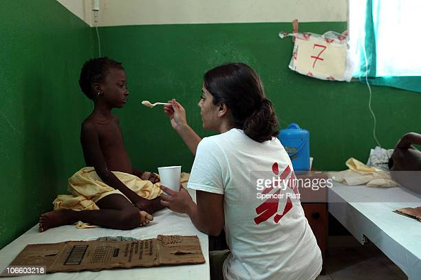 A doctor with Doctors Without Borders feeds a sick child with cholera in a clinic run by the Haitian government where Doctors Without Borders is...