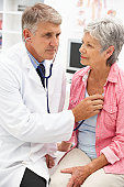 Doctor listening to female patient's heart