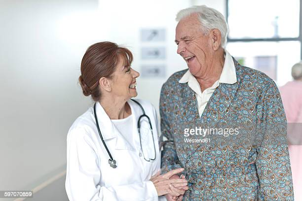 Doctor with happy elderly patient on hospital floor